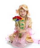 Flickan i en hatt och med blommor Royaltyfri Bild