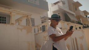 Flickan i en hatt och solglasögon gör selfie Flickan rymmer en telefon Mot bakgrunden av vita byggnader lager videofilmer