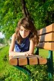 Flickan i en jeanklänning ligger på en bänk i parkera och läsningen Arkivbilder