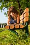 Flickan i en jeanklänning ligger på en bänk i parkera som läser a Royaltyfri Bild
