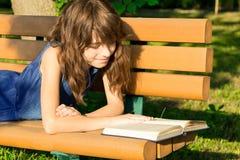 Flickan i en jeanklänning ligger på en bänk i parkera som läser a Arkivbilder