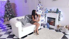 Flickan i en klänning sitter på soffan nära en julgran arkivfilmer
