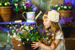 Flickan i en kräm- klänning med lila blommor Arkivfoto