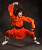 Flickan i en orange dräkt bär en uttrycksfull uppsättning av Wushu Royaltyfria Bilder