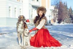 Flickan i en pälsväst och en röd klänning som går med hunden Royaltyfri Fotografi