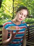 Flickan i en röd blus äter en paj Royaltyfri Bild