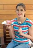 Flickan i en röd blus äter en paj Arkivbild