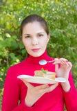 Flickan i en röd blus äter en paj Arkivfoto