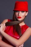 Flickan i en röd klänning Flicka i en röd hatt Royaltyfria Foton