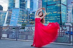 Flickan i en röd klänning på bakgrund av höghus I Arkivfoton