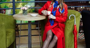 Flickan i en röd regnrock i fisknätstrumpbyxor, sitter i ett kafé över en kopp kaffe, bredvid den där är ett rött paraply royaltyfri fotografi