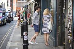 Flickan i en randig klänning och en pojke i ett randigt T-tröjaanseende nära lagret som ser, shoppar fönstret Fotografering för Bildbyråer