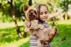 Flickan i en randig tröja ler och rymmer en liten hund Arkivfoto