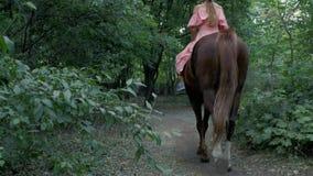 Flickan i en rosa klänning och hjälm rider en brun häst på bakgrunden av träd och lövverk tillbaka sikt 4K video 4K arkivfilmer