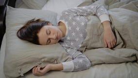 Flickan i en säng Den unga brunetten sover i eftermiddagen Kvinnan i grå pyjamas med stjärnor Brunetten arkivfilmer