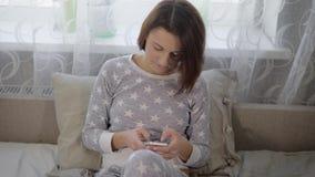 Flickan i en säng i ett sovrum Den unga brunetten sitter på en säng Kvinnan i grå pyjamas med stjärnor _ stock video