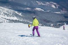 flickan i en skidadräkt går att skida Fotografering för Bildbyråer