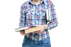 Flickan i en skjorta och jeans rymmer böcker i hennes händer vit isolat royaltyfria bilder