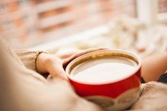 Flickan i en slags tvåsittssoffa stack tröjan som dricker kaffe från ett rött, rånar arkivfoto
