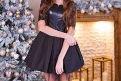 Flickan i en svart klänning står nära julgranen arkivfoto
