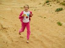 Flickan i en varm röd dräkt stöter ihop med sanden av havet Royaltyfria Foton
