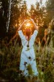 Flickan i en vit klänning ser solnedgången i skogen och kopplar av Kvinna med flätad trådfrisyren royaltyfri bild