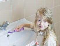 Flickan i ett badrum tvättar den elektriska tandborsten Arkivbild