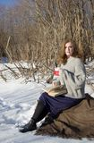 Flickan i ett grått omslag, en purpurfärgad kjol sitter i en vinterskog med en råna av varmt te i henne händer och läser en bok royaltyfria bilder