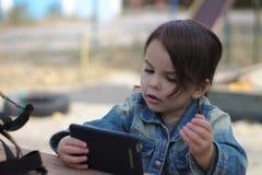 flickan i ett grov bomullstvillomslag rymmer i hennes händer och blickar in i smartphonen, medan sitta på en tabell på lekplatsen royaltyfria foton