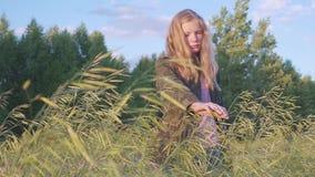 Flickan i ett kamouflageomslag trycker på en växt i en by arkivfilmer