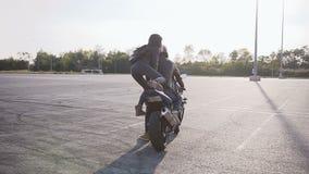 Flickan i ett läderomslag med en läderryggsäck på hennes skuldror, inställningar motorcykeln var hennes pojkvän är stock video