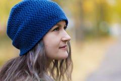 Flickan i ett lag och en blå hatt på en bakgrund av höstträd och lönnlöv royaltyfria bilder