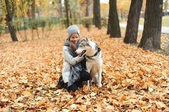 Flickan i ett lock med en hund i höst parkerar i aftonen arkivfoto