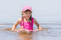 Flickan i ett lock sitter på den grunda floden i vatten Royaltyfri Bild
