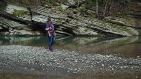 Flickan i ett purpurfärgat omslag, jeans och gymnastikskor irrar på en stenig ö på en sjö i bergen lager videofilmer