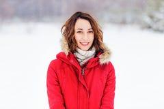 Flickan i ett rött lag går vinterdag Arkivbild
