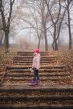 Flickan i ett rosa omslag som går i en dimmig skog för höst parkerar in arkivfoton