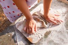 Flickan i ett vitt förkläde förbereder degen på en skärbräda royaltyfria foton