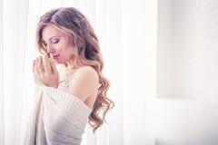Flickan i ett vitt omslag som rymmer koppen. Arkivbilder