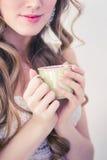 Flickan i ett vitt omslag som rymmer koppen. Royaltyfri Fotografi