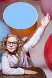 Flickan i exponeringsglas med den lyftta handen önskar att fråga Royaltyfri Foto