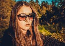 Flickan i exponeringsglas på bakgrunden av naturen arkivfoton