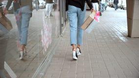 Flickan i flåsandekörningar på gatan med packar i handforntid shoppar stock video