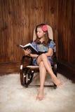 Flickan i forntida gungstol läser boken Arkivbild