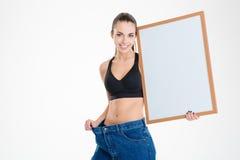 Flickan i gammal jeans blev det för stora innehavmellanrumsbrädet Royaltyfria Foton
