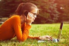 Flickan i gräs genom att använda bärbara datorn och ilar telefonen Arkivbilder