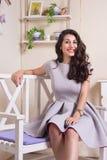 Flickan i grå färger klär sammanträde på en bänk arkivbild