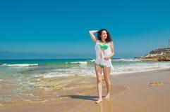 Flickan i grön bikini promenerar havet Fotografering för Bildbyråer