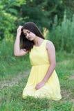 Flickan i gult klänningsammanträde på gräs Fotografering för Bildbyråer