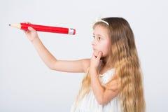 Flickan i hår sätter band med en stor blyertspenna Arkivbild